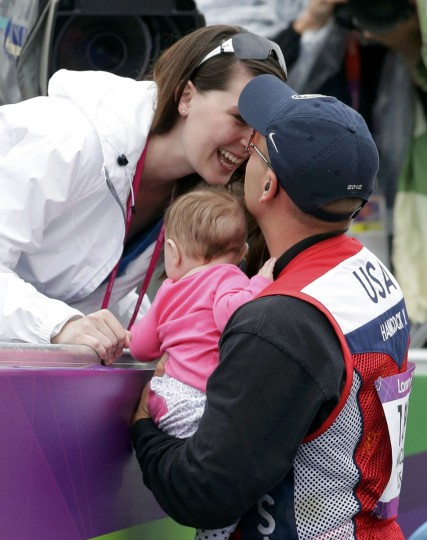 Vincent Hancock of the U.S. kisses his wife Rebekah as he holds their baby Brenlyn after he won the gold medal during the men's skeet finals at the Royal Artillery Barracks during the London 2012 Olympic Games July 31, 2012. (Cathal McNaughton/Reuters)