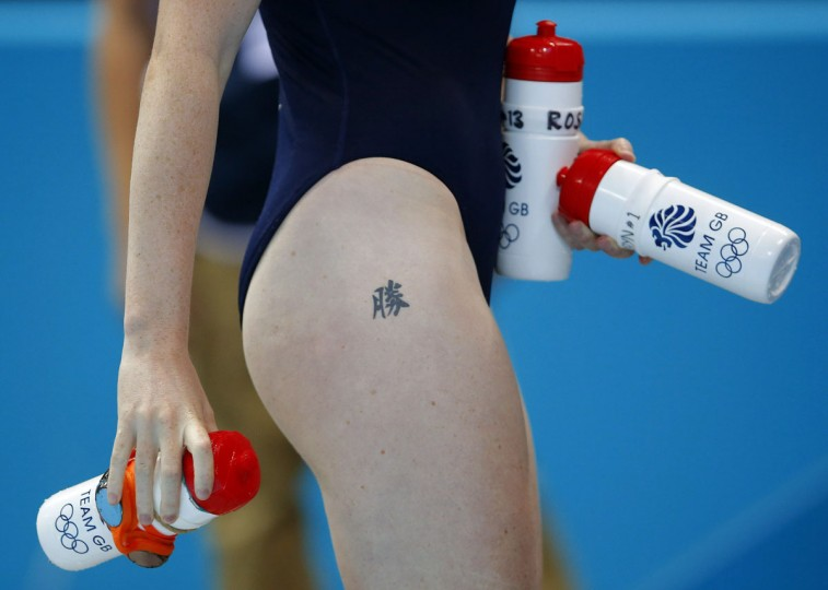 "A player of Britain carries bottles for her team mates during their women's preliminary round Group B water polo match against Italy at the London 2012 Olympic Games at the Water Polo Arena August 3, 2012. The tattoo on her leg reads: ""Victory."" (Laszlo Balogh/Reuters)"