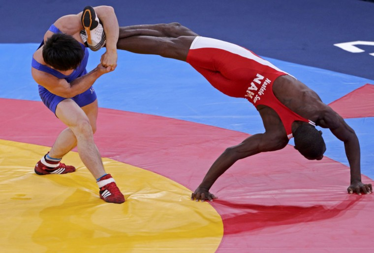 North Korea's Kyong Il Yang (in blue) fights with Namibia's Naatele Sem Shilimela on the repechage of the Men's 55Kg Freestyle wrestling at the ExCel venue during the London 2012 Olympic Games. (Toru Hanai/Reuters)