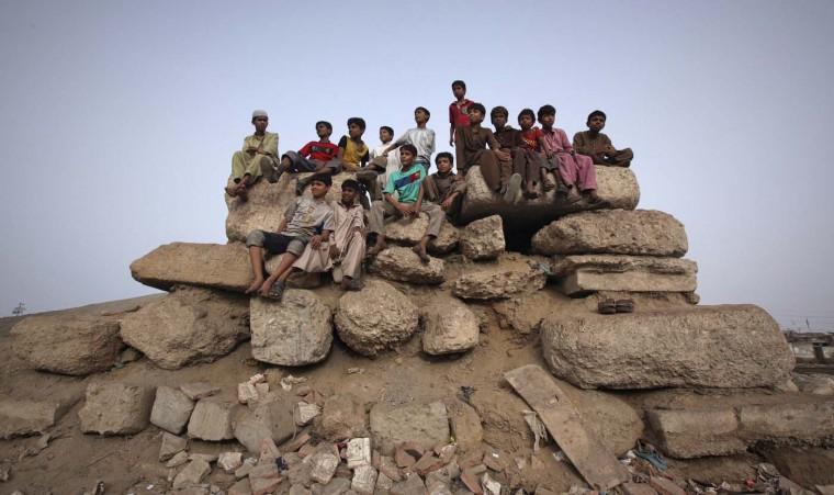 Children sit on cement blocks while watching a soccer match in a Karachi slum August 5, 2012. (Akhtar Soomro/Reuters)