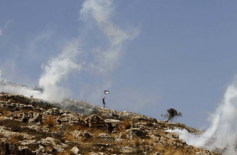 A Palestinian protester waves a flag as smoke from tear gas canisters fired by Israeli security forces rises during clashes at a protest against a nearby Jewish settlement, in the West Bank village of Nabi Saleh, near Ramallah August 31, 2012. (Mohamad Torokman/Reuters photo)