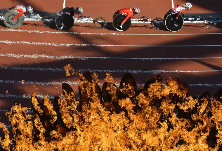 Competitors are seen through the Paralympic flame as they race during the Women's 5000m T54 classification heats at the Olympic Stadium during the London 2012 Paralympic Games August 31, 2012. (Toby Melville/Reuters photo)