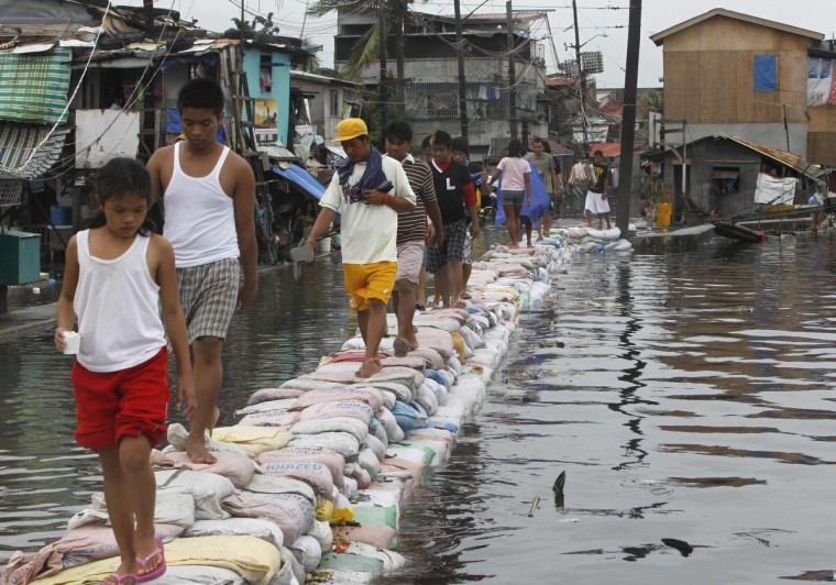Residents use sandbags to cross to another street after floodwaters, brought on by last week's monsoon rains, damaged the river wall in Navotas city, metro Manila. More than 100 people were killed and at least two million people were affected in nearly two weeks of steady monsoon rains, according to disaster officials. (Romeo Ranoco/Reuters)