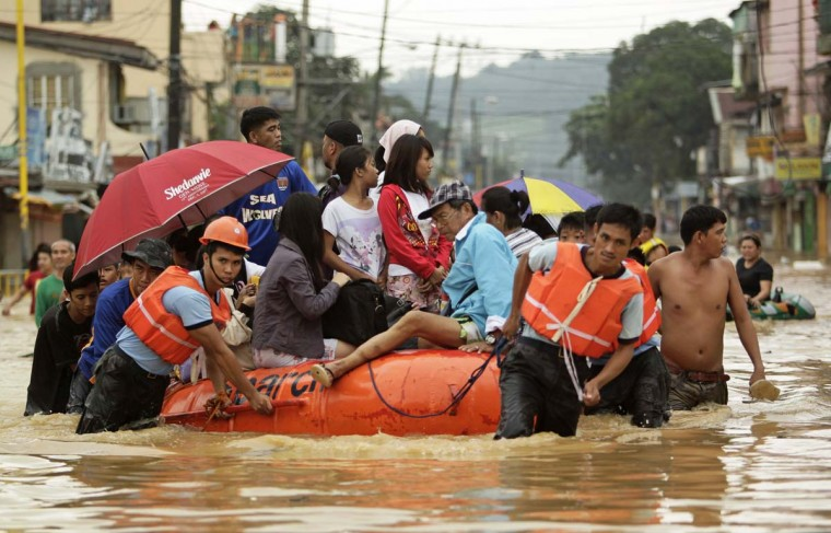 Rescuers evacuate residents along a flooded street in Marikina city, Metro Manila. Large parts of Manila were still swamped in floods after continuous rains pounded the capital overnight. (Tim Chong/Reuters photo)