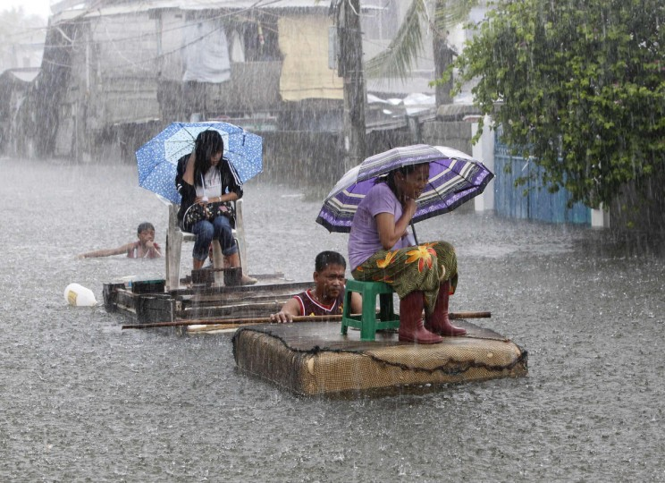 Residents ride on makeshift rafts during a heavy downpour along a flooded street in Malabon, Metro Manila. Typhoon Saola (Gener) is likely to stay in Philippine territory until Friday, the Philippine Atmospheric Geophysical and Astronomical Services Administration (PAGASA) said on Wednesday, and the National Disaster Risk and Reduction Council said the death toll from Gener stood at 12 and one person was reported missing.(Erik De Castro/Reuters)