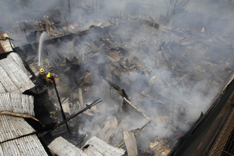 Firefighters extinguish a fire at a squatter colony in Pasay city, metro Manila. The fire razed at least 200 shanty houses on Wednesday with no casualty reported, according to local media. (Romeo Ranoco/Reuters)