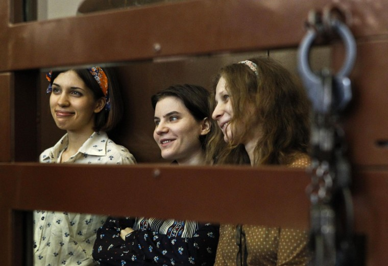 "MOSCOW, RUSSIA - AUGUST 3: Nadezhda Tolokonnikova (L), Yekaterina Samutsevich and Maria Alyokhina (R), members of female punk band ""Pussy Riot"", attend their trial inside the defendents' cell in a court in Moscow August 3, 2012. (Maxim Shemetov/Reuters)"