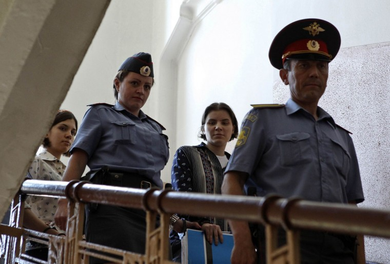 "MOSCOW, RUSSIA - AUGUST 3: Yekaterina Samutsevich (2nd R) and Nadezhda Tolokonnikova (L), members of female punk band ""Pussy Riot"", are escorted by police to a court in Moscow August 3, 2012. (Maxim Shemetov/Reuters)"