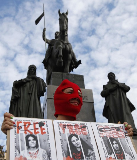 PRAGUE, CZECH REPUBLIC - AUGUST 17: An activist wears a mask whole holding a sign in support of members of the female punk band Pussy Riot and holds a banner during a protest rally at the Venceslas Square in Prague August 17, 2012. (David W. Cerny/Reuters)