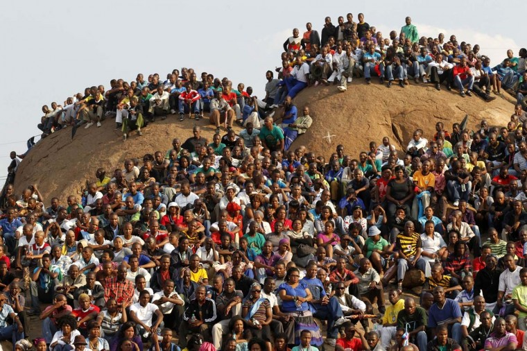 """Mining community gathers at a hill dubbed the """"Hill of Horror"""" during a memorial service for miners killed during clashes at Lonmin's Marikana platinum mine in Rustenburg, 100 km (62 miles) northwest of Johannesburg,. South Africans held a memorial service at a platinum mine where police shot dead 34 strikers. (Siphiwe Sibeko/Reuters photo)"""