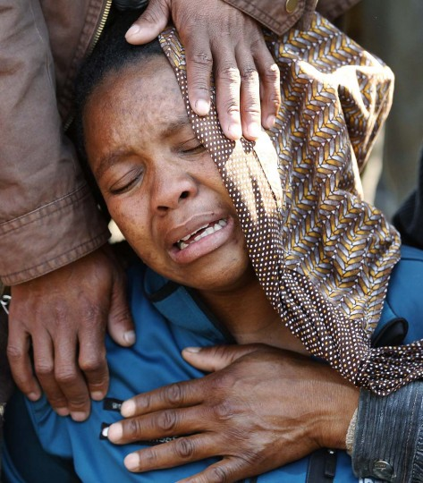 A relative is comforted ahead of memorial services for miners killed during clashes at Lonmin's Marikana platinum mine in Rustenburg, 100 km (62 miles) northwest of Johannesburg. (Siphiwe Sibeko/Reuters photo)