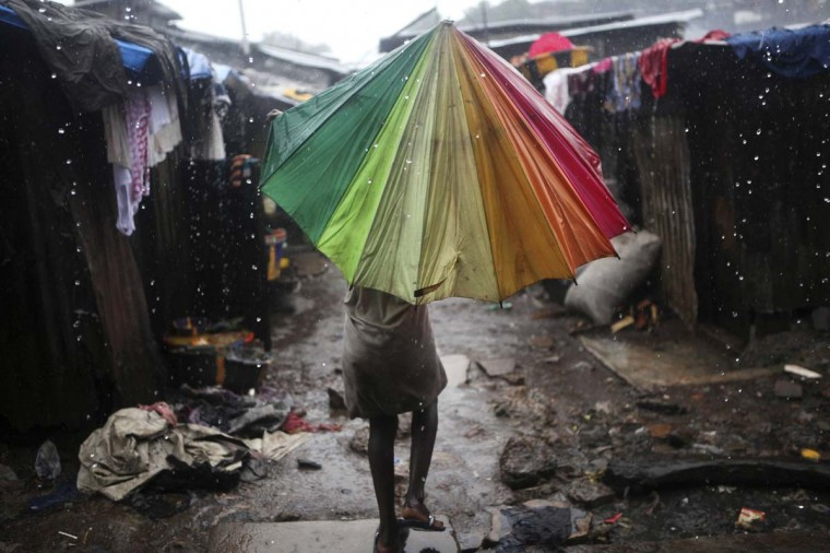 """A child carries an umbrella in pouring rain in the slum of Susan's Bay in Sierra Leone's capital Freetown. Sierra Leone's government has described the current cholera outbreak in the West African state as a """"national emergency."""" At the height of the wet season, over-populated areas with poor water and sanitation are exacerbating the spread of the disease. (Simon Akam/Reuters photo) ("""