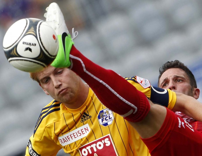 FC Thun's Enrico Schirinzi (R) fights for the ball with FC Luzern's (FCL) Florian Stahel during their Swiss Super League soccer match in Thun August 5, 2012. (Thomas Hodel/Reuters)