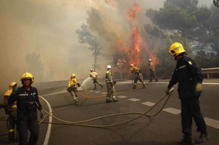 Firefighter try to extinguish a fire in a forest on the road between Marbella and Monda in Ojen, near Malaga, southern Spain August 31, 2012. A wildfire raging out of control along southern Spain's Costa del Sol killed one man, injured several people and forced the evacuation of thousands on the edge of the upmarket tourist resort of Marbella, regional authorities said on Friday. (Jon Nazca/Reuters photo)