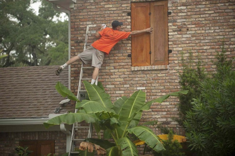 Jason Preston closes shutters as Hurricane Isaac approaches Gulfport, Mississippi. (Michael Spooneybarger/Reuters photo)