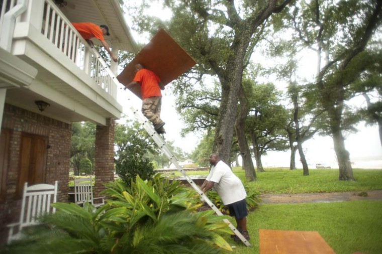 Jason Preston, Jermaine McNair and James Hayes put up shutters on a house as Hurricane Isaac approaches Gulfport, Mississippi. (Michael Spooneybarger/Reuters photo)