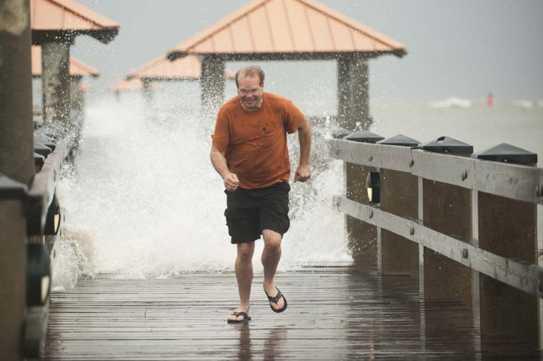 Scott Burley runs from crashing surf on the Ken Combs Pier as Hurricane Isaac approaches Gulfport, Mississippi. (Michael Spooneybarger/Reuters photo)