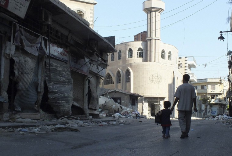A man walks with his child at the Qusour area after Syrian President Bashar al-Assad forces shelled the neighbourhood in the central of Homs city August 5, 2012. (Yazan Homsy/Reuters)