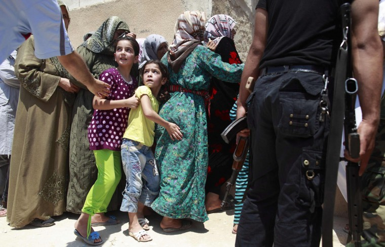 Girls queue to buy bread at the only bakery serving the outskirts of Idlib province August 1, 2012. (Zohra Bensemra/Reuters)