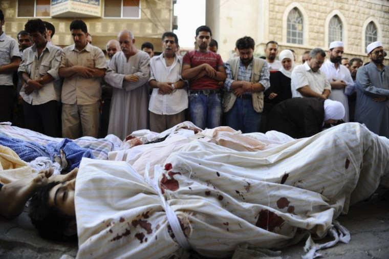Residents pray over the bodies of Syrians who they say are opposition activists killed by forces loyal to Syria's President Bashar al-Assad, during a mass funeral along a street in Jdeidet Artouz near Damascus August 1, 2012. (Hussam Chamy/Reuters)