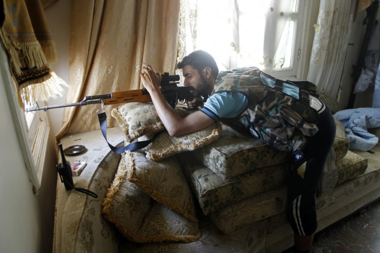 A Free Syrian Army sniper looks through the sight on his rifle inside a house in Aleppo August 13, 2012. (Goran Tomasevic/Reuters)