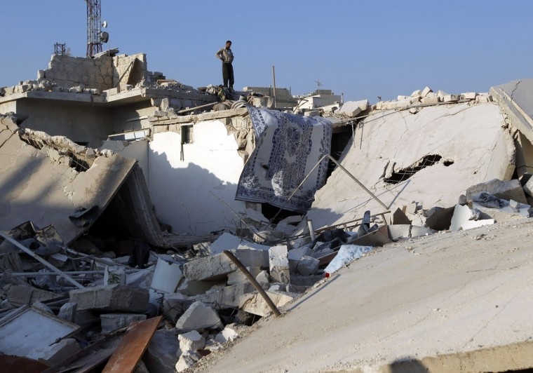 A man stands on a house destroyed during a recent Syrian Air force air strike in Azaz, some 47 km (29 miles) north of Aleppo, August 15, 2012. (Goran Tomasevic/Reuters)