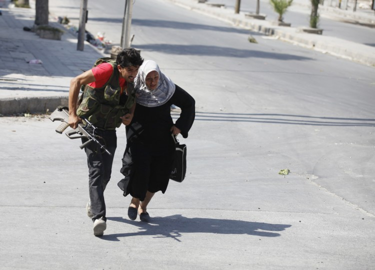 A Free Syrian Army fighter helps a woman to run across a street during clashes in Aleppo August 12, 2012. (Goran Tomasevic/Reuters)