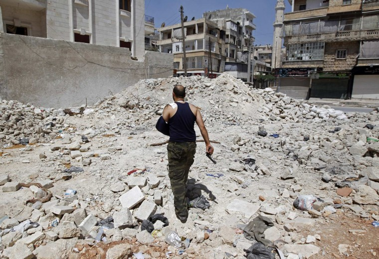 A wounded Free Syrian Army commander walks through rubble in the Salaheddine neighborhood of central Aleppo August 11, 2012.(Goran Tomasevic/Reuters)
