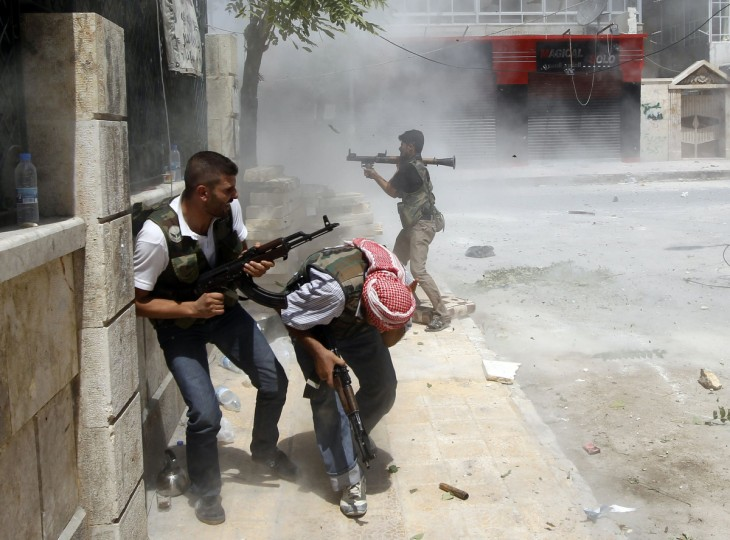 A Free Syrian Army fighter fires a RPG as a Syrian Army tank shell hits a building across a street during heavy fighting in the Salaheddine neighbourhood of central Aleppo August 11, 2012. (Goran Tomasevic/Reuters)