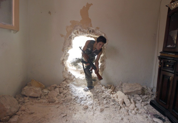 A Free Syrian Army fighter walks through a hole in a wall of a house during heavy fighting in Salaheddine neighborhood of central Aleppo August 11, 2012. (Goran Tomasevic/Reuters)