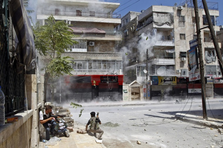 Free Syrian Army fighters take cover as a Syrian Army tank shell hits a building across a street during heavy fighting walks in the Salaheddine neighbourhood of central Aleppo August 11, 2012. (Goran Tomasevic/Reuters)