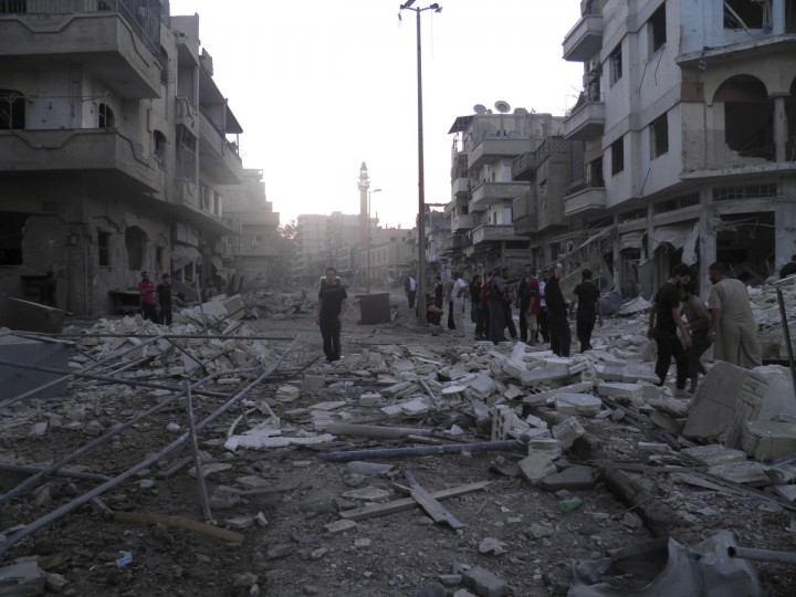 Residents stand among the ruins of buildings destroyed in what activists said was an air strike by the Syrian Air Force at al-Khalidiah neighborhood in Homs August 11, 2012. (Shaam News Network/Reuters)