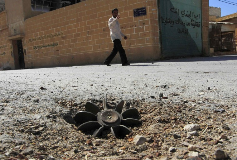 A man waves as he walks past an unexploded mortar embedded along a street after shelling by forces loyal to Syrian President Bashar al Assad in the centre of Anadan, 15 km (9.3 miles) northwest of Aleppo, August 8, 2012. (Zohra Bensemra/Reuters)