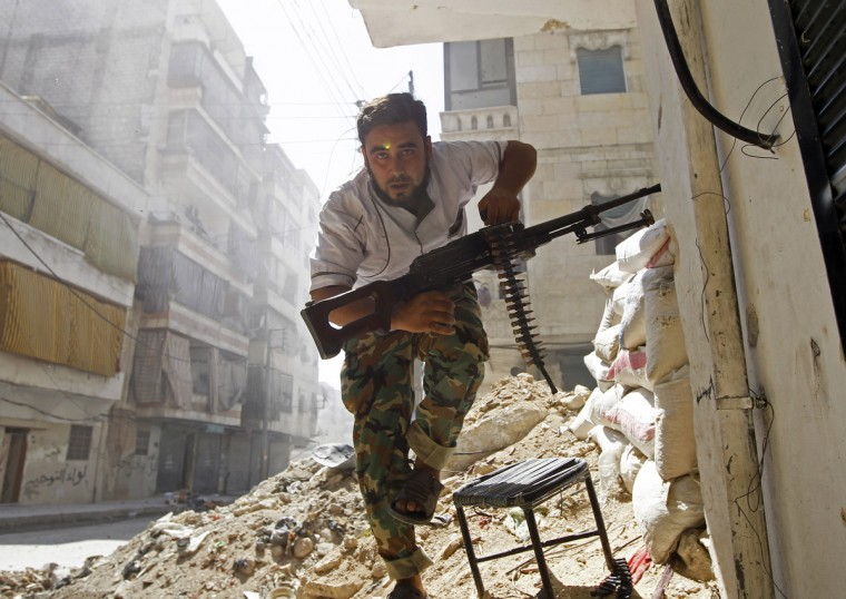 A Free Syrian Army fighter takes cover during clashes with Syrian Army in the Salaheddine neighbourhood of central Aleppo August 7, 2012. (Goran Tomasevic/Reuters)