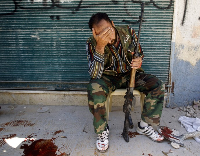 A Free Syrian Army fighter reacts after his friend was shot by Syrian Army soldiers during clashes in Salah al-Din neighborhood in central Aleppo August 4, 2012. (Goran Tomasevic/Reuters)