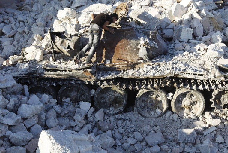 A man looks at a destroyed Syrian Army tank in Azaz, some 47 km (29 miles) north of Aleppo August 3, 2012. (Goran Tomasevic/Reuters)