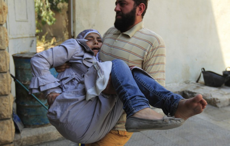 A member of the Free Syrian Army carries an injured civilian after shelling by forces loyal to President Bashar Al-Assad in Aleppo's disctrict of Salah Edinne July 31, 2012. (Zohra Bensemra/Reuters)