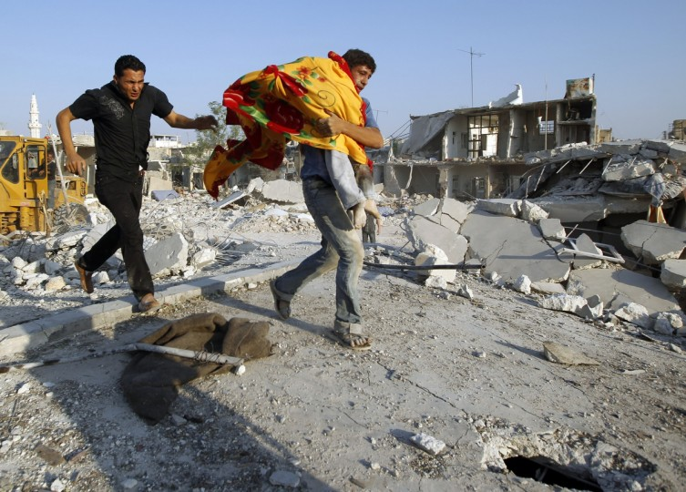 A man carries the body of a boy after a Syrian Air force air strike in Azaz, some 47 km (29 miles) north of Aleppo, August 15, 2012. (Goran Tomasevic/Reuters)