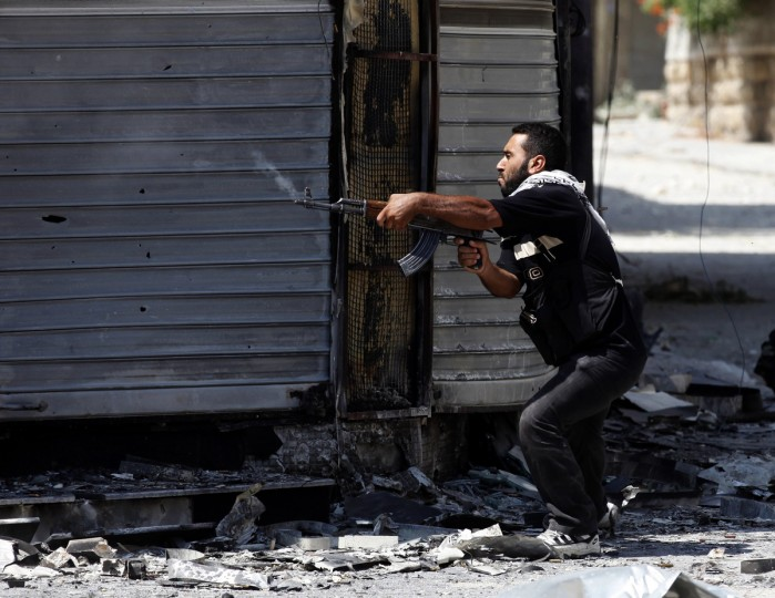 A Free Syrian Army fighter fires an AK-47 rifle in Aleppo August 15, 2012. (Goran Tomasevic/Reuters)