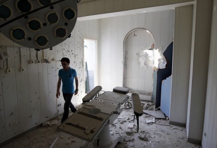 A man walks through a room at Dar Al Shifa Hospital, damaged in yesterday's Syrian Air force air strike, in the Sha'aar neighbourhood of Aleppo August 15, 2012. The patients that were in the hospital when the air strike happened have now all been evacuated. (Goran Tomasevic/Reuters)