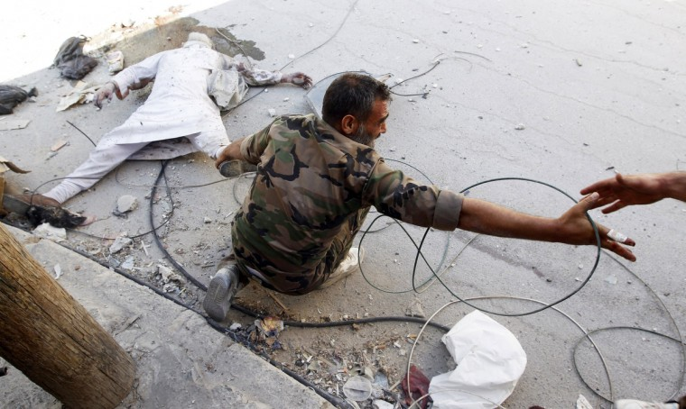 A Free Syrian Army fighter drags a dead man shot in Salaheddine neighborhood in Aleppo out of the line of sniper fire August 13, 2012. Free Syrian Army fighters said the man was shot dead by Syrian Army snipers. (Goran Tomasevic/Reuters)