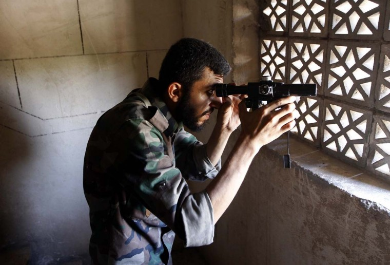 A Free Syrian Army fighter observes the area during clashes in Aleppo. (Goran Tomasevic/Reuters photo)
