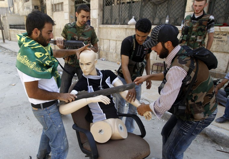 Free Syrian Army fighters dress a mannequin to looks like a fighter during clashes in the Salaheddine neighbourhood of central Aleppo, Syria. (Goran Tomasevic/Reuters)