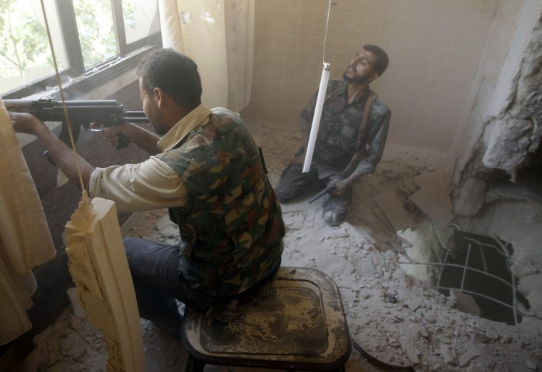 A Free Syrian Army fighter fires an AK-47 rifle in Aleppo August 14, 2012. (Goran Tomasevic/Reuters)