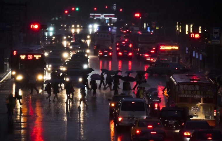 People walk across an intersection during heavy rain as Typhoon Tembin approaches Taiwan in Taipei. Taiwan issued a warning for torrential rain and strong winds and put its military on standby as typhoon Tembin headed for the island's east coast with winds of around 145 km/hour after soaking parts of the Philippines. (Yi-ting Chung/Reuters photo)
