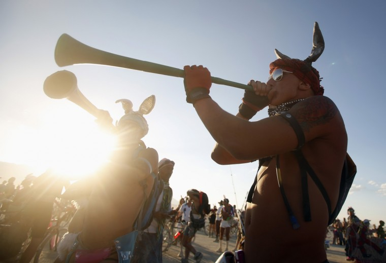"""Bender, his name on the Playa, plays a horn of the Playa during the Burning Man 2012 """"Fertility 2.0"""" arts and music festival in the Black Rock Desert of Nevada. (Jim Urquhart/Reuters)"""