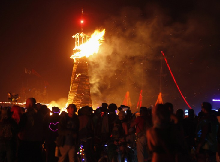 "Participants watch as artwork that is part of the Circle of Regional Effigies is burned during the Burning Man 2012 ""Fertility 2.0"" arts and music festival in the Black Rock Desert of Nevada. (Jim Urquhart/Reuters)"
