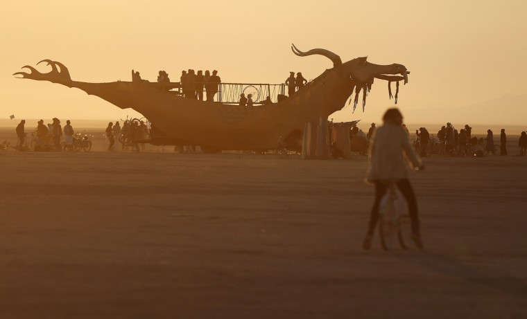 "Participants watch the sunrise from an art car during the Burning Man 2012 ""Fertility 2.0"" arts and music festival. (Jim Urquhart/Reuters)"