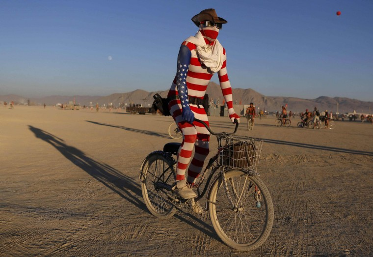 """""""Nick"""", his playa name, rides across the desert during the Burning Man 2012 """"Fertility 2.0"""" arts and music festival in the Black Rock Desert of Nevada. (Jim Urquhart/Reuters)"""