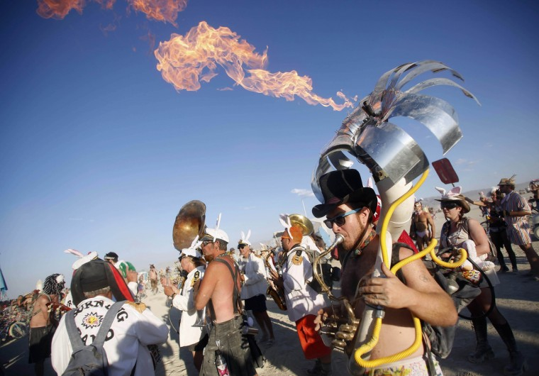 """Eric Yttri plays a flaming tuba during the Burning Man 2012 """"Fertility 2.0"""" arts and music festival in the Black Rock Desert of Nevada. (Jim Urquhart/Reuters)"""